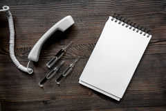 Llame por teléfono al microteléfono, a la ampolla y al cuaderno en mofa de escritorio de madera oscura del doctor de la llamada d Fotos de archivo libres de regalías