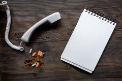 Llame por teléfono al microteléfono, a las píldoras multicoloras y al cuaderno en mofa de escritorio de madera oscura del doctor  Fotos de archivo