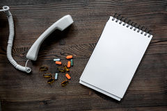 Llame por teléfono al microteléfono, a las píldoras y al cuaderno en mofa de escritorio de madera oscura del doctor de la llamada Imágenes de archivo libres de regalías