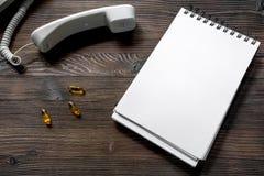 Llame por teléfono al microteléfono, a los oills y al cuaderno en mofa de escritorio de madera oscura del doctor de la llamada de Fotos de archivo