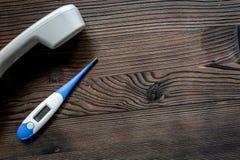 Llame por teléfono al microteléfono y al termómetro en llamada de escritorio de madera oscura de la visión un espacio del doctor  Fotos de archivo libres de regalías