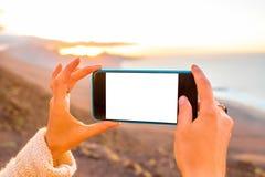 Llame por teléfono con la pantalla blanca en el fondo del paisaje de la isla Fotografía de archivo