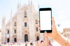 Llame por teléfono con la pantalla blanca en fondo de la catedral del Duomo Imágenes de archivo libres de regalías