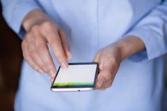 Llame por teléfono en manos femeninas con el primer de la pantalla en blanco Imagenes de archivo