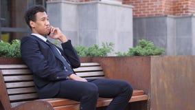 Llame por teléfono a la charla, hombre de negocios africano Attending Call mientras que se sienta en banco almacen de metraje de vídeo