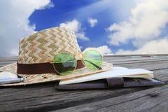 Llame por teléfono, las gafas de sol y sombrero de paja verdes en un puente de madera imagen de archivo