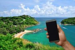 Llame por teléfono a mano con la pantalla en blanco en el CCB hermoso de la ubicación del viaje Foto de archivo
