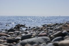 Llanbedrog, Wales, the UK - pebbles and blue shiny waters on a sunny day. royalty free stock photography