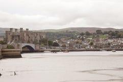 LLandudno, País de Gales, Reino Unido - 27 de mayo de 2018 río que fluye al lado del castillo Barcos que flotan en el río Puente  fotografía de archivo libre de regalías