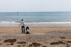 LLandudno, Walia, UK - MAJA 27, 2018 ojciec z dzieckiem w dziecko frachtu odprowadzeniu na plaży Samotny rodzic z dzieckiem na se zdjęcia royalty free