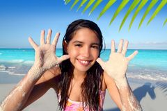 Llatin teen girl playing beach smiling sandy hands. Latin indian teen girl playing beach showing sandy hands in Caribbean tropical sea Stock Photo