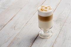 Llatte macchiato kawa na białym drewnianym tle z kopii przestrzenią obraz stock