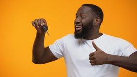 Llave afroamericana emocionada del coche de la tenencia del hombre y el mostrar pulgares para arriba, compra almacen de metraje de vídeo