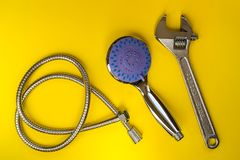 Llave ajustable del metal, nueva cabezal de ducha y manguera flexible en un fondo amarillo Cabezal de ducha del PDA con con el in foto de archivo libre de regalías