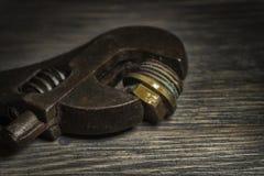 Llave ajustable en un fondo de madera rústico fotografía de archivo
