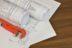 Llave ajustable y dibujos en la mesa foto de archivo