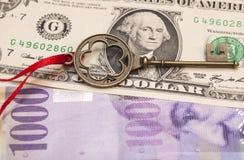 Llave al éxito con el arco rojo en dólares de un americano y Swi 1000 Foto de archivo libre de regalías