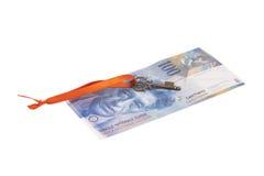 Llave al éxito con el arco rojo en nota del franco suizo Imagen de archivo libre de regalías