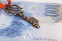 Llave al éxito con el arco rojo en nota del franco suizo Foto de archivo