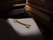 Llave amarilla de la puerta en el libro abierto en el fondo de una pila de libros viejos Imágenes de archivo libres de regalías