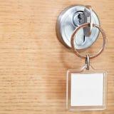 Llave con llavero cuadrado en blanco en cierre de la cerradura para arriba Fotos de archivo