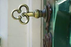 Llave de cobre amarillo en una puerta vieja verde Fotografía de archivo