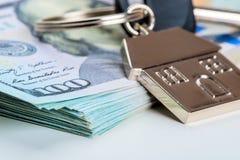 Llave de la casa en una pila de dólares americanos en un fondo blanco fotografía de archivo libre de regalías