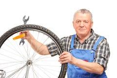 Llave de la explotación agrícola del hombre y reparación de la rueda de bicicleta Fotografía de archivo
