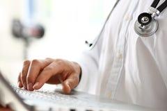 Llave de la prensa de la mano del doctor de la medicina en el teclado de ordenador portátil Fotografía de archivo libre de regalías