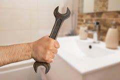 Llave de la tenencia del hombre en cuarto de baño imagen de archivo