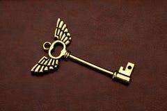 Llave de oro con las alas en el cuero de Brown Foto de archivo libre de regalías