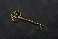 Llave de oro hermosa en fondo negro del Grunge Imágenes de archivo libres de regalías