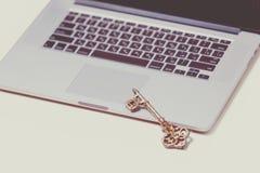 Llave de oro hermosa y ordenador portátil de plata fresco en el perno maravilloso Imagen de archivo libre de regalías