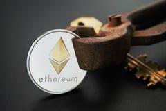Llave de oro de la moneda de plata de Ethereum y pinzas oxidadas Imágenes de archivo libres de regalías