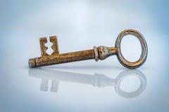 Llave de oro de la puerta del vintage en un fondo azul Imagen de archivo libre de regalías