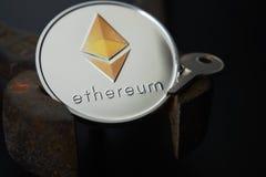 Llave de plata de la moneda de Ethereum y pinzas oxidadas del vintage Fotografía de archivo libre de regalías