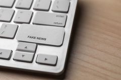 Llave de teclado de ordenador con NOTICIAS FALSAS de la frase en la tabla de madera imágenes de archivo libres de regalías