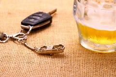 Llave del coche con accidente y la taza de cerveza Imagen de archivo libre de regalías