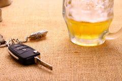 Llave del coche con accidente y la taza de cerveza Foto de archivo libre de regalías