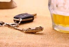 Llave del coche con accidente y la taza de cerveza Foto de archivo