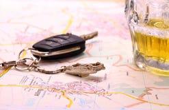 Llave del coche con accidente y la taza de cerveza en mapa Fotografía de archivo
