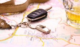Llave del coche con accidente y la taza de cerveza en mapa Imagen de archivo libre de regalías