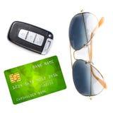 Llave del coche con teledirigido, gafas de sol y tarjeta de crédito, aislada Imagen de archivo