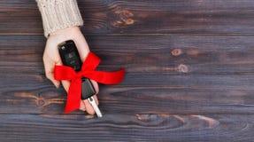 Llave del coche del control de la mano de la mujer con el arco rojo Donante de un coche como bandera del regalo imagen de archivo