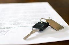 Llave del coche en un contrato de venta firmado Imágenes de archivo libres de regalías