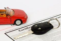 Llave del coche en un documento del seguro Foto de archivo libre de regalías
