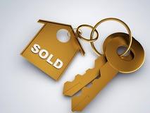 Llave del oro con el hogar vendido Fotos de archivo libres de regalías