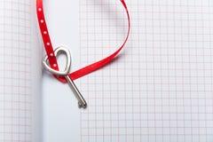 Llave en forma de corazón en el cuaderno Fotos de archivo