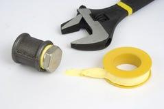 Llave inglesa ajustable y cinta amarilla Fotografía de archivo