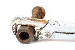 Llave inglesa ajustable y tornillo oxidado con una tuerca Foto de archivo
